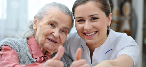 caregiver and senior woman raising their thumb